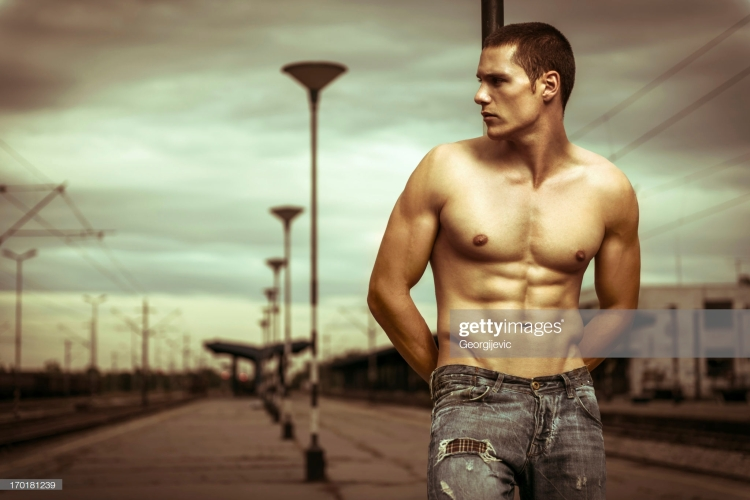Attractive shirtless male model posing on the railway station.